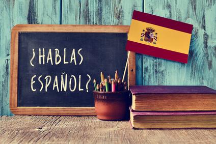 Hablas espanol auf Tafel geschrieben mit spanischer Flagge anbei