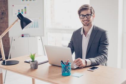 Junger Mann sitzt im Büro am Schreibtisch vor PC