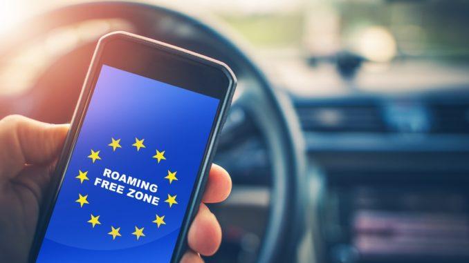 Mann hält Smartphone mit Schriftzug Roaming Free Zone