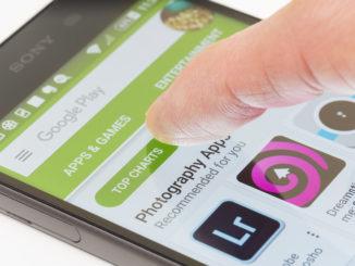 Finger tippt auf Smartphone im Google Play Store