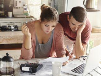 verschuldetes junges paar sitzt vor laptop