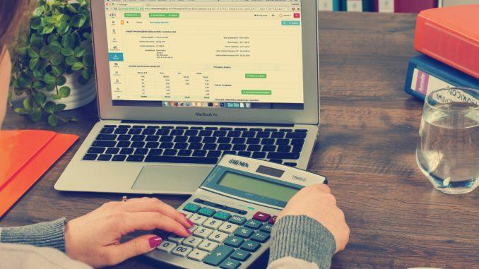 Ein Laptop und ein Taschenrechner für die Lohnbuchhaltung